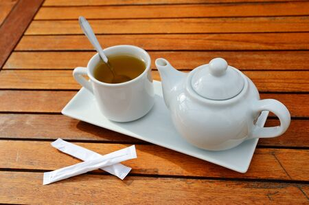 The drinking set for tea is placed on the wooden surface of the table.