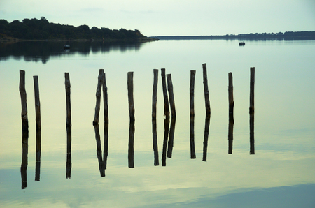 pales: The sky and the row of the wooden pillars are reflected on the still water surface