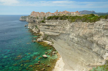 There are transparent water, the white overhang cliffs and the limestone rocks in the seashore of Corsica island. The old town of Bonifacio is on the background.