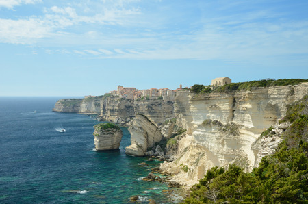 overhang: There are transparent water, limestone rocks and the white overhang cliffs in the seashore of the Corsica island. The remote town Bonifacio is on the background.