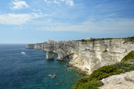 There are transparent water, limestone rocks and the white overhang cliffs in the seashore of the Corsica island. The remote town Bonifacio is on the background.