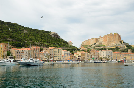 There are many various vessels in the harbor, residential buildings on the narrow shelf in the bottom part of Bonifacio and the medieval fortress on the cliff from above. Editorial