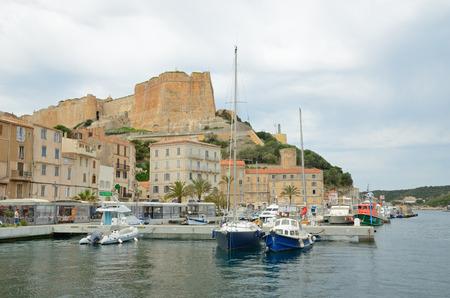 literas: Hay muchos diversos buques en el puerto, edificios residenciales en la parte inferior de Bonifacio y la fortaleza medieval en el acantilado desde arriba.