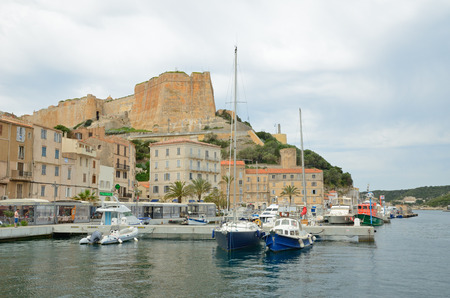 literas: There are many various vessels in the harbor, residential buildings in the bottom part of Bonifacio and the medieval fortress on the cliff from above. Editorial
