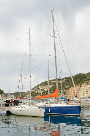 literas: Two yachts are moored near the berth in the harbor of the Mediterranean coastal town Bonifacio.