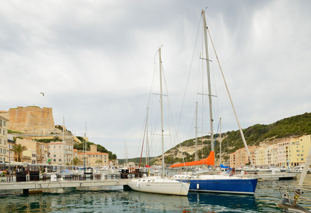 speedboats: There are many various vessels in the harbor, residential buildings on the narrow shelf in the bottom part of Bonifacio and the medieval fortress on the cliff from above. Editorial