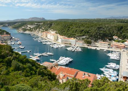 literas: Hay muchos barcos en el puerto y los edificios residenciales en la estrecha plataforma bajo acantilados verdes en la parte inferior de Bonifacio.
