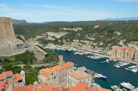 literas: There are many vessels in the harbor, residential buildings on the narrow shelf under the green cliffs in the bottom part of Bonifacio and the medieval fortress from above. Editorial