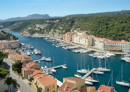 literas: Hay muchos barcos en el puerto y los edificios residenciales en la estrecha plataforma bajo las colinas verdes en la parte inferior de Bonifacio.