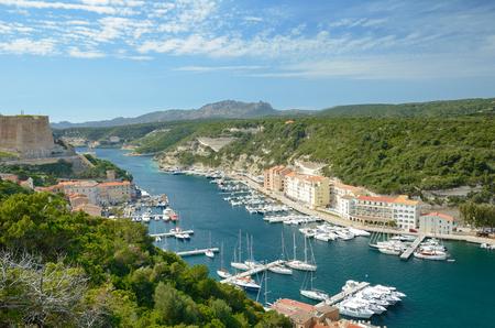 literas: Hay muchos barcos en el puerto, edificios residenciales en la estrecha plataforma bajo las colinas verdes en la parte inferior de Bonifacio y la fortaleza medieval desde arriba.