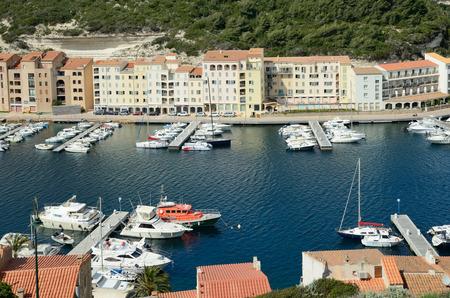 literas: Hay muchos barcos en el puerto y los edificios residenciales en la estrecha plataforma en la parte inferior de Bonifacio. Editorial