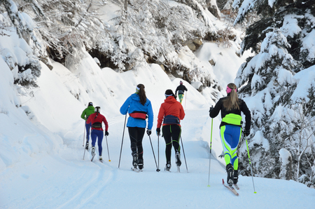 Several women are skiing at the groomed trail in the snowy forest. Marcadau valley is a favorite place for cross-country skiing and snow shoeing at both sides of Gave Marcadau in the Pyrenees national park. Archivio Fotografico