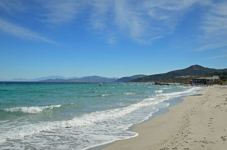 forested: LIle Rousse is a lively resort town in the Corsican coast. A man with a child are walking on the wide sandy beach. There are the Mediterranean sea and remote capes forested. Stock Photo