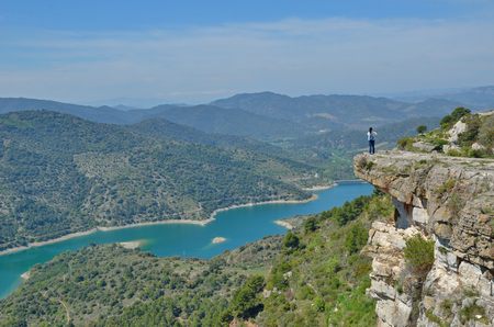 forested: A tourist is on the escarpment above the river Embalsa with the artificial lake in the green valley. Prades mountains is a large calcareous mountain massif heavily forested.