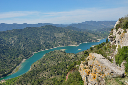 A limestone slabs are on the top of cliff above the river Embalsa with the artificial lake in the green valley. Prades mountains is a large calcareous massif heavily forested. Stock Photo