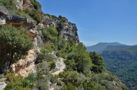 The rocky pass is along the abrupt cliff with lush foliage. Siurana is a world-class climbing destination. There are steep walls, slabs, overhangs and other limestone landforms in Prades mountains. Stock Photo