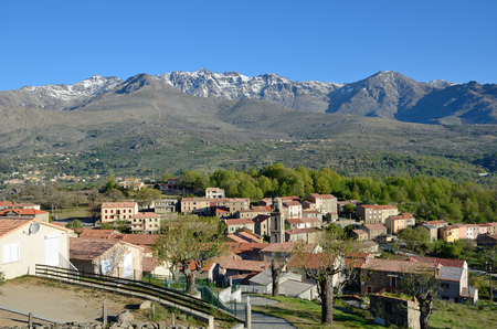 Corsican village Casamaccioli is situated on the slopes of the mountain massif in the natural park of Corsica. There is the ridge of Cinto in the background. Stock Photo