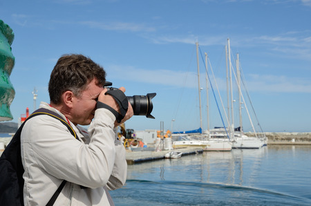 A man is taking a photo in the fishing port Saint-Florent. It is a popular vacation spot for many tourists on the Mediterranean coast.