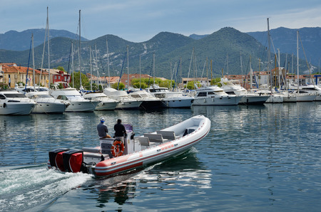 speedboats: A pleasure-boat is floating along the berth with many modern vessels in the Corsican port Saint-Florent. It is a popular vacation spot for many tourists on the Mediterranean coast.
