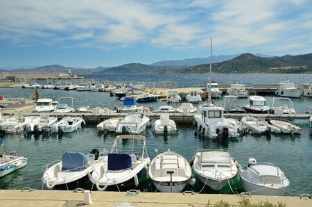 There are many various vessels in the natural harbor of the coastal town LIle Rousse. It is a lively resort with easy access to many places on the north-west Corsican coast. Stock Photo