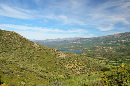Balagne is also called the garden of Corsica. In the foreground there is a flat hill covered with maguis. There are a fertile plain with fields and remote mountains in the background.