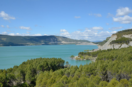 Embalse de Yesa is a beautiful artificial reservoir on the border of Navarre and Aragon. There are opaque blue water and unusual rocky shore forested with pine woods.