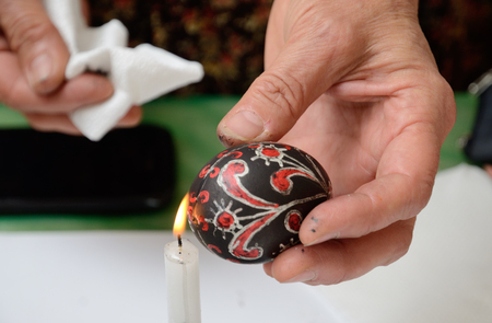 A human hand is heating the painted wax-resisted egg near the flame of the candle burning.