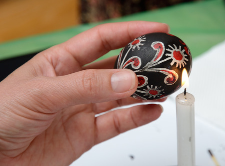 easter candle is burning: A human hand is heating the painted wax-resisted egg near the flame of the candle burning.