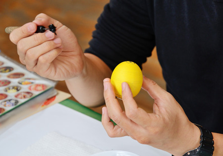 stylus: The male hands are holding a stylus and a yellow dyed egg. The Easter egg is decorated with a pattern using a wax-resist method. Stock Photo