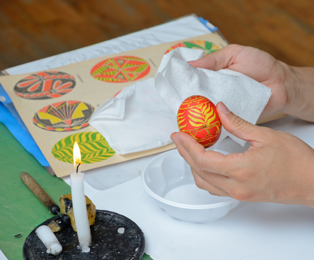 easter candle is burning: The human hands are wiping the ready painted egg near the candle burning. The Easter egg is decorated with a pattern using a wax-resist method. Stock Photo