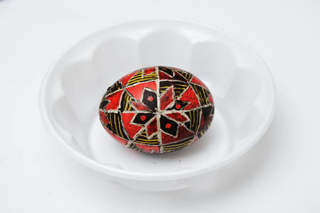 An Easter egg is decorated with traditional Ukrainian folk ornament using a wax-resist method. The pysanka is covered with wax and dyed red, black and yellow colores. 스톡 콘텐츠