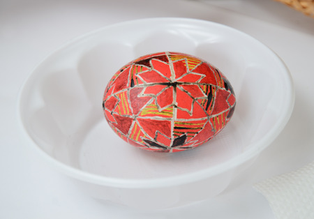An Easter egg is decorated with traditional Ukrainian folk ornament using a wax-resist method. The pysanka is covered with wax and dyed red and yellow colores.