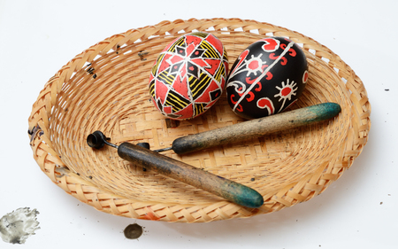 stylus: The two ready pysankas are lying in the basket. There are also pisachokes inside. The Easter eggs are decorated with traditional Ukrainian folk ornament using a wax-resist method.