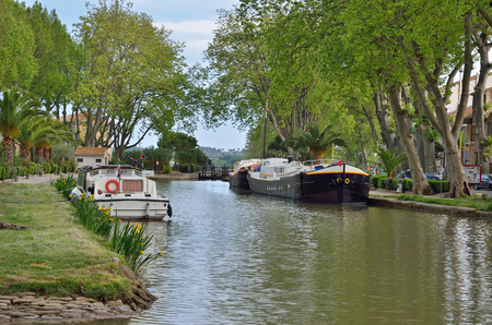A barge and a motorboat are moored near the gateway. The Canal de Jonction runs through the French town Salleles dAude. This is a part of the La Nouvelle branch of the Canal du Midi. Stok Fotoğraf