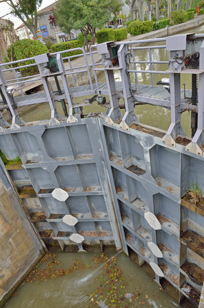 The lock is used for lowering a watercraft on the canal de Jonction in the French town Salleles dAude.