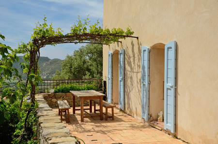 The stone patio with a grapevine roof is in the famous Corsican town Pigna. There are a wooden table with two benches and a mountain peak in the background.