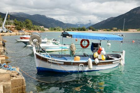 fishing rig: The small fishing boats are moored near the stone berth in the Corsican bay of Sagone. Stock Photo
