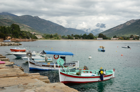 The small fishing boats are moored near the stone berth in the Corsican bay of Sagone. Stock Photo