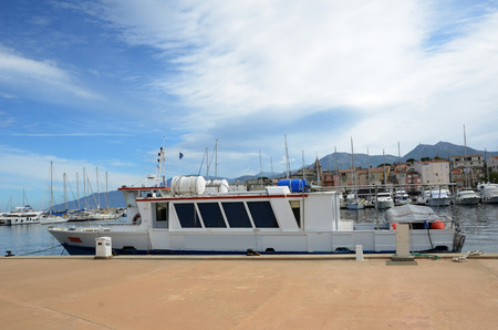 A pleasure-boat is moored at the berth in the Corsican port Saint-Florent. It is a popular vacation spot for many tourists on the Mediterranean coast.