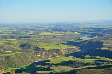 The fertile flatland is photographed from above in spring. There are a canyon carved with a bent river, an artificial lake, many fields and plantations. Stock Photo