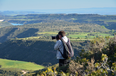 The male-tourist is photographing the fertile flatland from above in spring. There are a canyon carved with a bent river, many fields and plantations.