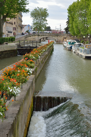 The lock is used on the canal de la Robine in the ancient French city Narbonne. It is the third section of the La Nouvelle branch. Banco de Imagens - 78804387