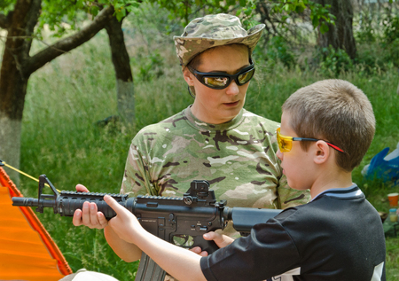The preteen boy is trained by the instructor at the outdoor shooting range during Stok Fotoğraf - 86660293