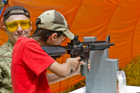 The teenage boy is trained by the instructor at the outdoor shooting range during