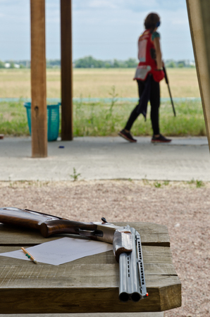 A shotgun, a sheet of paper and a pencil are on the table. In the background there is a shooter at the clay target shooting.