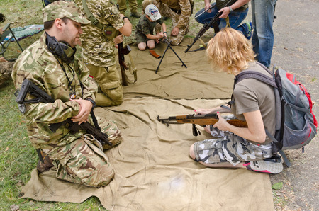 The civil man, woman and child are trained by the instructors at the outdoor shooting range during