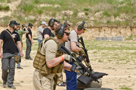 The civil men are trained by the coach at the outdoor shooting range during