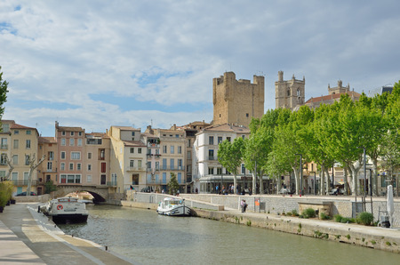 The canal de la Robine runs through the center of the French city Narbonne. There are the traditional townhouses and ancient towers behind, the passerby and a green alley, several yachts at the pier.