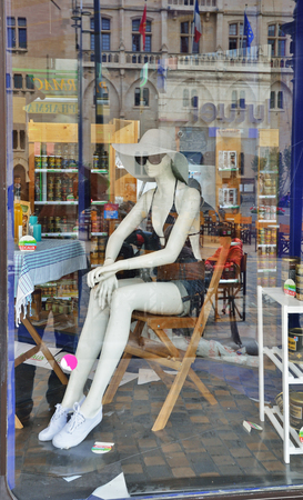 Een vrouwelijke ledenpop zit in de showcase. De oude gebouwen en voorbijgangers worden weerspiegeld op het glazen oppervlak van de winkel in de Franse stad.