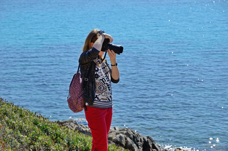 A young woman is taking a photo on the background of the blue sea. She is on the green slope.